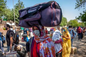 Indians wearing protective masks stand with their luggage in queue outside a railway station [image: Alamy]