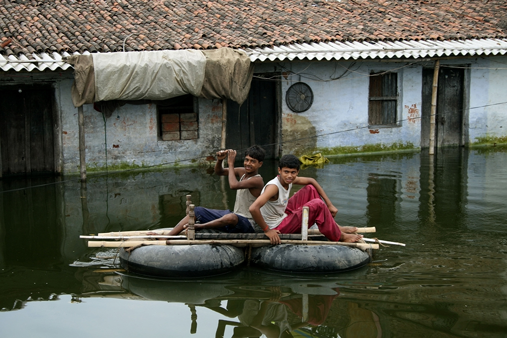 two boys float on tyres and wood across the water.  Much of Patna, the capital of Bihar, was flooded for over a fortnight last year [image by: Louise Batalla Duran/Alamy]