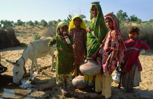 Mother and daughters collecting water from the village well in the arid region of Thar desert, Pakistan Sindh province.