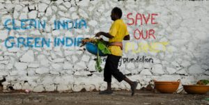 Man cleaning beach in India. Wall with background text 'Clean India, Green India' and 'Save our Planet'