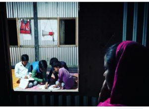 A woman looks on as children study at the library in the char [image by: Rituparna Neog]