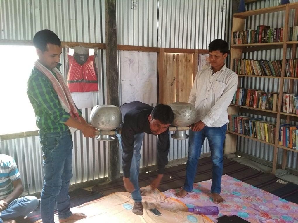 जोरहाट और पुस्तकालय के जलग्रहण क्षेत्र से सामुदायिक कार्यकर्ता यह बता रहे हैं कि बाढ़ से बचने के लिए आसानी से उपलब्ध सामग्री का उपयोग कैसे करें [image by: Abdul Kalam Azad]