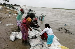 Residents of Thakurbari place sand-filled bags on the Koshi riverbank in an effort to save the riverbank and their homes from floodwaters [Image by: Birat Anupam]