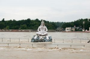 A statue of the Hindu god Shiva in the middle of the Ganga river, which overflowed due to heavy rains in Rishikesh, Uttarakhand, in 2011 [image by: Scarabea / Alamy]