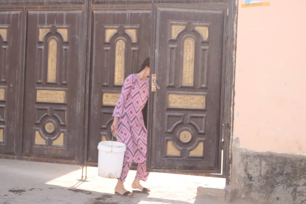 A Dushanbe resident carries water home [Image by: Firuza Karimova]