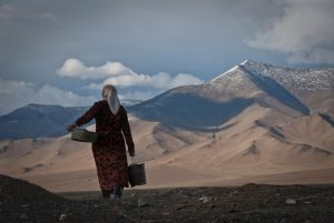 Woman carrying water from Karakul Lake in Tajikistan [Image by: Alamy]