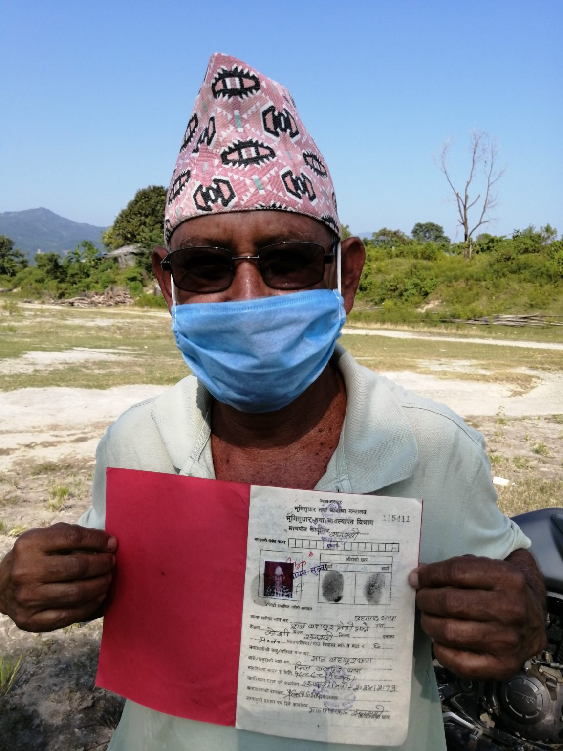 Prahlad Thapa with the document proving his ownership of land [Image by: Birat Anupam]