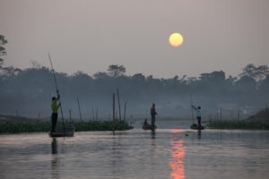 Fishers returning at sunset from the Brahmaputra to their homes inside Dibru Saikhowa National Park