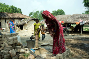 Woman pumping water from a hand borewell in Varanasi, Uttar Pradesh, in the Ganga basin in India. (Photo credit: Dinodia Photos/Alamy S)