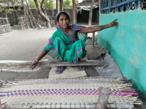 55-year-old Rudridevi Sardar making a mat in front of her home. She sustains herself with mat-making using wetland materials from Koshi Tappu Wildlife Reserve [image by: Birat Anupam]
