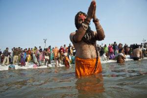 A Sadhu praying to the sun in the Ganga river at the 2013 Kumbh Mela at Allahabad, India. [Image: Alamy]