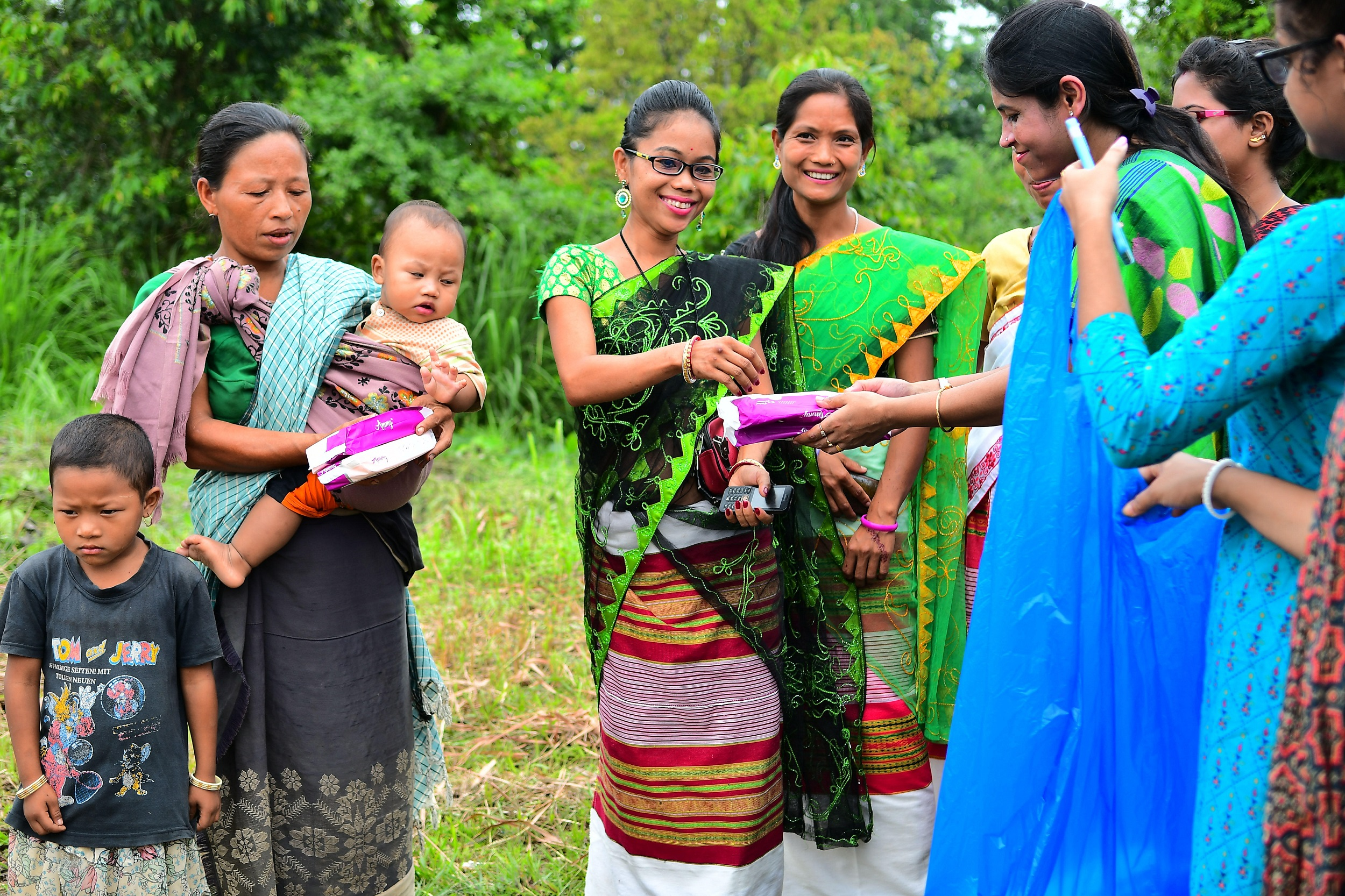 Health workers distributing free sanitary pads to the women and girls in the Indian state of Tripura and explaining to them the necessary of using it, in a health camp. [image by: Abhisek Saha / SOPA Images / ZUMA Wire / Alamy Live News]