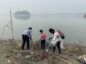 Volunteers from The Midway Journey pick up trash from the Brahmaputra riverbank in Guwahati [Image by: Kasturi Das]