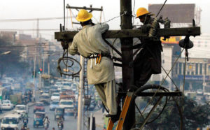 This 2013 photo shows Pakistani technicians fixing an electricity tower in Lahore. Today, the country is in the midst of a debate about the future of its power sector as it confronts huge electricity payments amidst persistent blackouts [Image: Alamy]