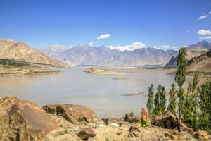 A solitary woman, covered in traditional head scarf, walking towards the Indus River near Skardu in Northern Pakistan [image: Alamy]