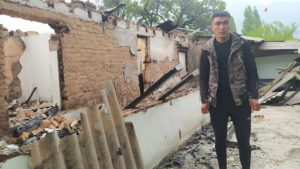 Mirlan Piridin, 26, stands in front of the destroyed house where he lived with his parents, in the border village Ak-Sai, Batken region, Kyrgyzstan. Hours before the house was destroyed by an artillery shell, the family managed to evacuate (Image: The Third Pole)