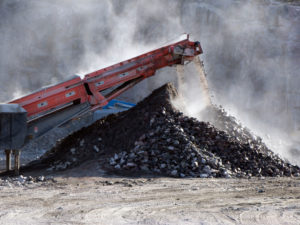 Crushed stones pile up below a conveyor belt from a stone crusher