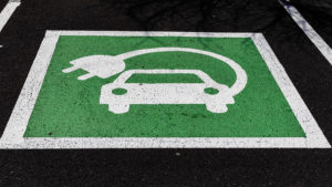 Green electric vehicle parking sign, painted on asphalt