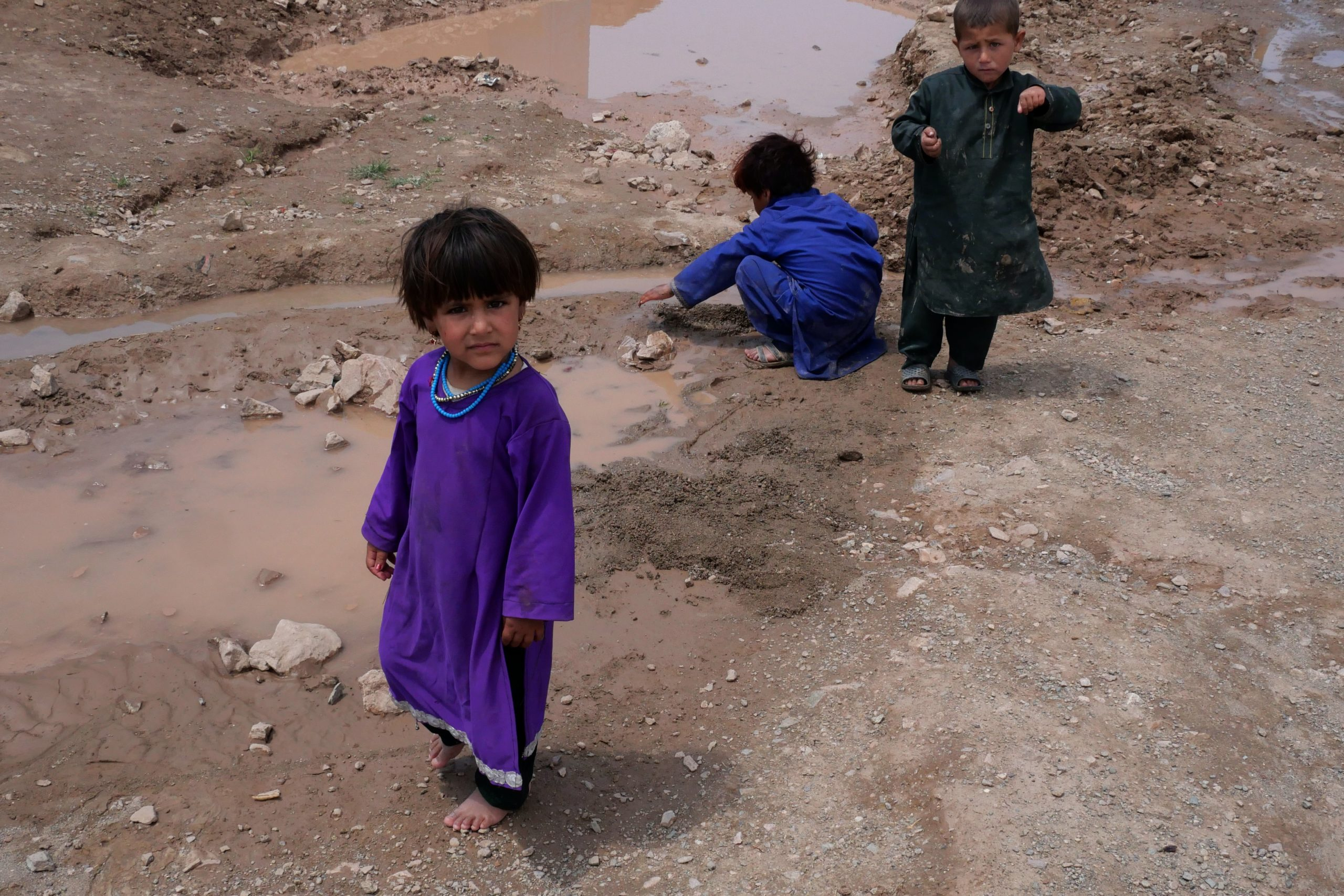Afghan children play in the mud in an unofficial camp for internally displaced people in Herat, Afghanistan (Image: Charlie Faulkner)