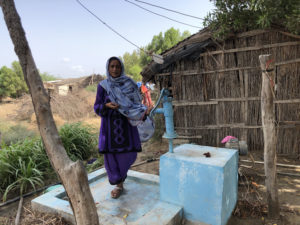 Malda Barkat stands next to a hand pump near her house in the village of Rato Khan Rind, in Thatta district. The intermittent supply means villagers must fetch water from a distance on a donkey cart (Image: Zofeen Ebrahim)