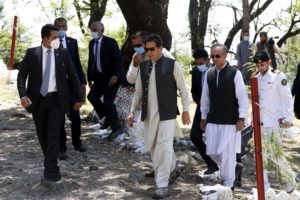 Pakistani Prime Minister Imran Khan (C) returns from where he planted a tree during an event in connection with the 10 Billion Tree Tsunami program in the country's northwest city of Haripur on May 27, 2021
