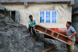 Men retrieve possessions from a house hit by flash flooding along the bank of Melamchi River in Sindhupalchok, Nepal, Navesh Chitrakar