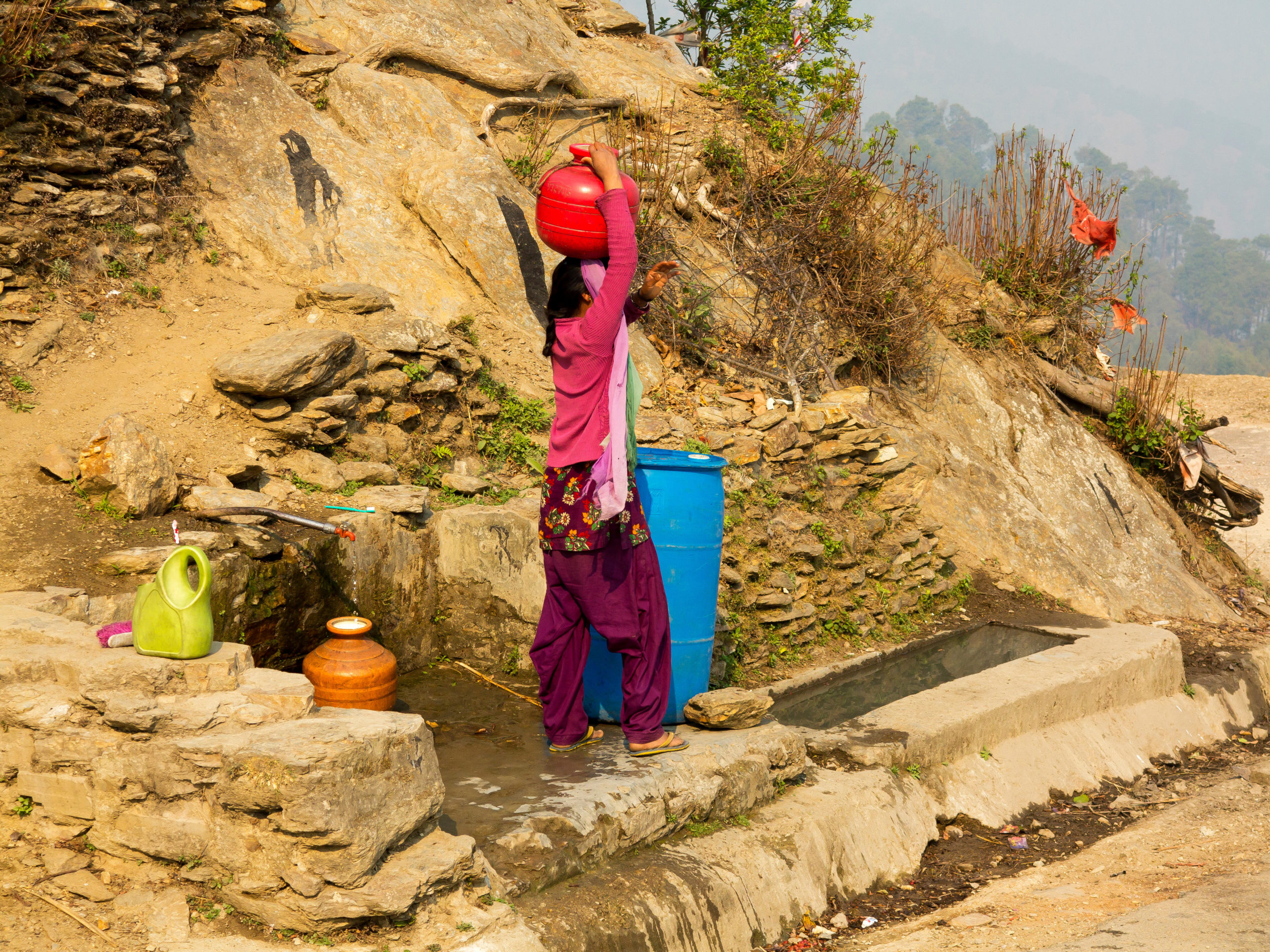 A woman fetches water from a spring at Tula Kote village in the Kumaon hills, Uttarakhand (Image: Fernando Quevedo de Oliveira / Alamy)