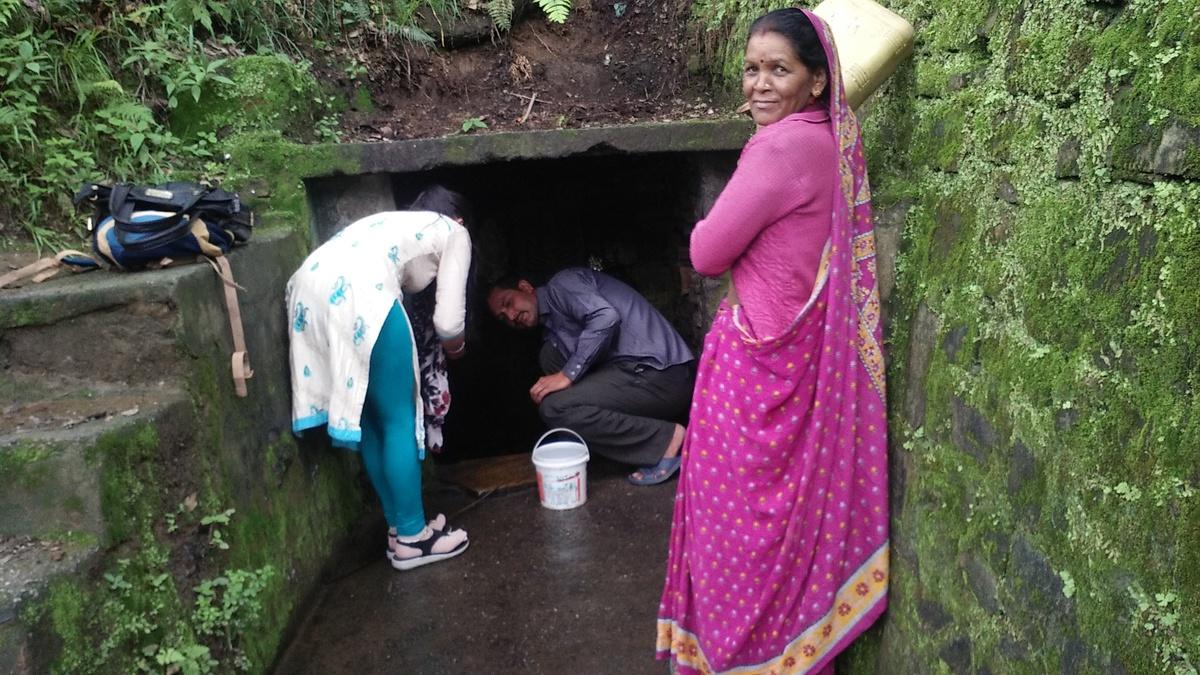 Committee members monitor the Mandir Naula spring's discharge in Nathuakhan, Nainital, Uttarakhand, CHIRAG