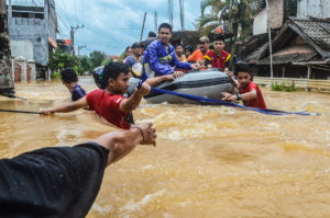 Rescuers evacuate residents from their flooded houses in Paccerakkang, Makassar, South Sulawesi, Indonesia