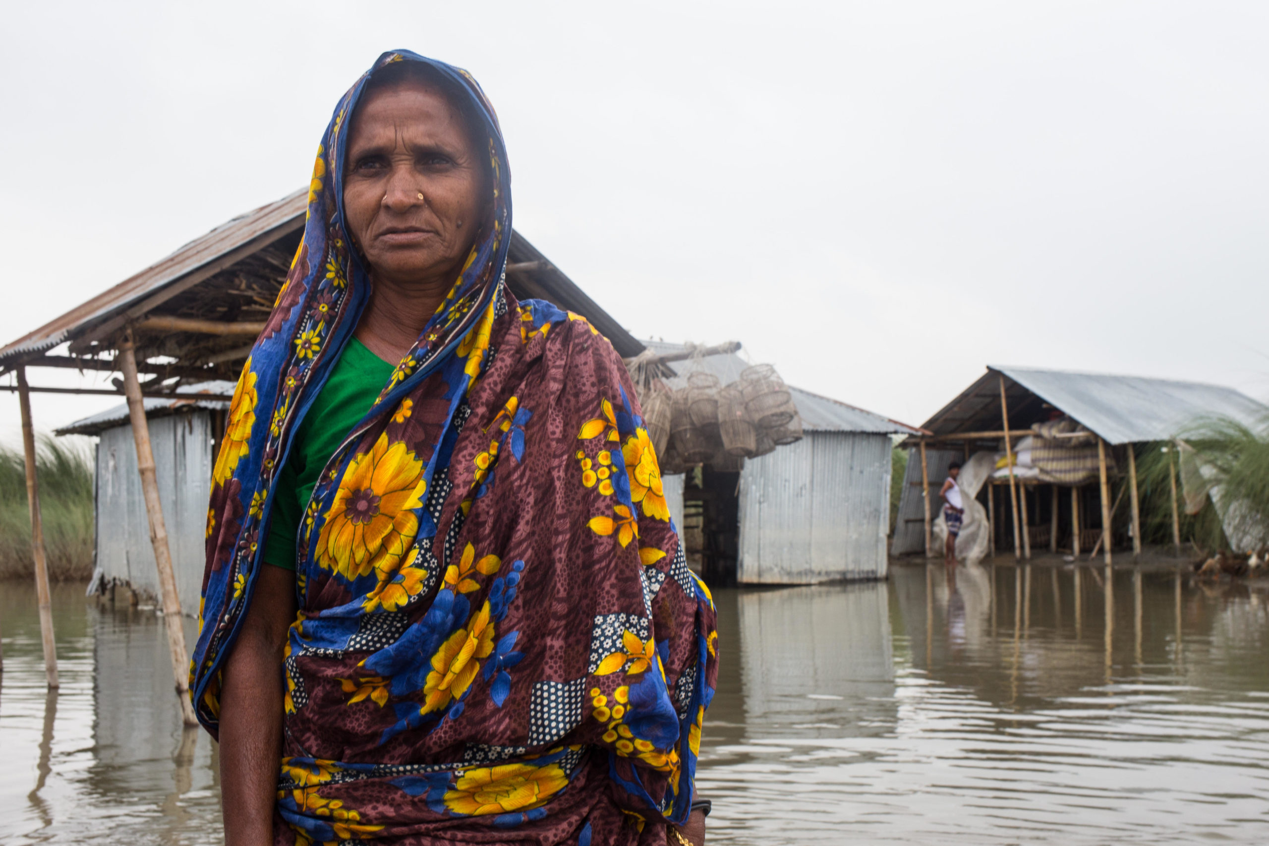 A Bangladeshi woman stands in front of flooded buildings in 2019. Research indicates that women, children and the elderly are most vulnerable to poor mental health after disasters. (Image: Md. Rakibul Hasan / Alamy)