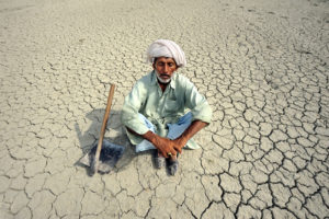 A farmer in Punjab, Pakistan, sits on the dry soil. More severe and frequent droughts are making it harder for people to grow crops where they have traditionally farmed.