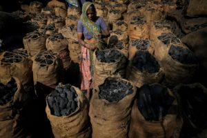 Woman loading charcoal in Ahmedabad, Gujarat, India. There will be little progress in combating climate change at COP26 unless millions of people are helped to move away from their dependence on the fossil fuel economy. (Image: Alamy)