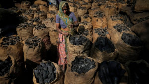 Woman charcoal Ahmedabad Gujarat India climate change fossil fuel coal economic growth and job security